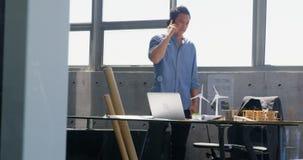 Μπροστινή άποψη της ασιατικής αρσενικής ομιλίας αρχιτεκτόνων στο κινητό τηλέφωνο σε ένα σύγχρονο γραφείο 4k φιλμ μικρού μήκους