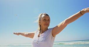 Μπροστινή άποψη της ενεργού ανώτερης καυκάσιας γυναίκας που εκτελεί τη γιόγκα στην παραλία 4k απόθεμα βίντεο