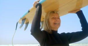 Μπροστινή άποψη της ενεργού ανώτερης καυκάσιας θηλυκής φέρνοντας ιστιοσανίδας surfer στο κεφάλι της στην παραλία 4k απόθεμα βίντεο