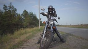 Μπροστινή άποψη της επιτυχούς βέβαιας νέας γυναίκας στη συνεδρίαση φορεμάτων δέρματος στο ποδήλατό της στο δρόμο Χόμπι, ταξίδι φιλμ μικρού μήκους