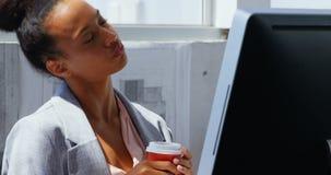 Μπροστινή άποψη της επιχειρηματία αφροαμερικάνων που εργάζεται στον υπολογιστή στο γραφείο σε ένα σύγχρονο γραφείο 4k απόθεμα βίντεο
