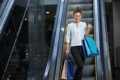 Μπροστινή άποψη της ευτυχούς γυναίκας με την απόλαυση των νέων αγορών στη λεωφόρο στοκ φωτογραφίες