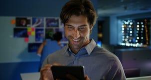 Μπροστινή άποψη της ευτυχούς νέας καυκάσιας αρσενικής εκτελεστικής εργασίας στην ψηφιακή ταμπλέτα στο σύγχρονο γραφείο 4k φιλμ μικρού μήκους