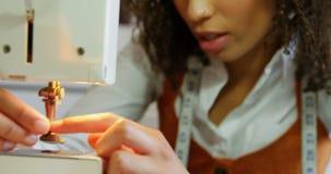 Μπροστινή άποψη της θηλυκής εργασίας σχεδιαστών μόδας αφροαμερικάνων με τη ράβοντας μηχανή στο εργαστήριο 4k φιλμ μικρού μήκους
