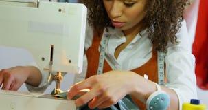 Μπροστινή άποψη της θηλυκής εργασίας σχεδιαστών μόδας αφροαμερικάνων με τη ράβοντας μηχανή στο εργαστήριο 4k απόθεμα βίντεο
