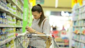 Μπροστινή άποψη της κατάπληξης της νέας γυναίκας με το κάρρο αγορών που αγοράζει τις υγιείς παιδικές τροφές στην υπεραγορά που στ απόθεμα βίντεο