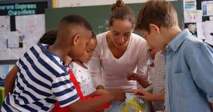 Μπροστινή άποψη της καυκάσιας θηλυκής εξήγησης δασκάλων για τη σφαίρα στην τάξη 4k φιλμ μικρού μήκους