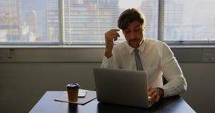 Μπροστινή άποψη της κουρασμένης νέας καυκάσιας αρσενικής εκτελεστικής εργασίας στο lap-top στο γραφείο σε ένα σύγχρονο γραφείο 4k απόθεμα βίντεο