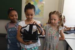 Μπροστινή άποψη της μαθήτριας με τους συμμαθητές που κρατούν και που φαίνονται κάσκα εικονικής πραγματικότητας στην τάξη στοκ εικόνα