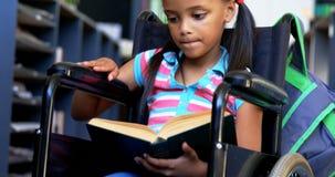 Μπροστινή άποψη της με ειδικές ανάγκες μαθήτριας αφροαμερικάνων που διαβάζει ένα βιβλίο στη βιβλιοθήκη στο σχολείο 4k απόθεμα βίντεο