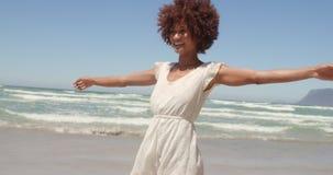 Μπροστινή άποψη της νέας γυναίκας αφροαμερικάνων που έχει τη διασκέδαση στην παραλία στην ηλιοφάνεια 4k φιλμ μικρού μήκους