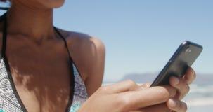 Μπροστινή άποψη της νέας γυναίκας αφροαμερικάνων στο μπικίνι που χρησιμοποιεί το κινητό τηλέφωνο στην παραλία 4k φιλμ μικρού μήκους