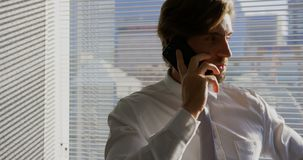 Μπροστινή άποψη της νέας καυκάσιας αρσενικής εκτελεστικής ομιλίας στο κινητό τηλέφωνο σε ένα σύγχρονο γραφείο 4k φιλμ μικρού μήκους
