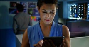 Μπροστινή άποψη της νέας καυκάσιας θηλυκής εκτελεστικής εργασίας στην ψηφιακή ταμπλέτα στο σύγχρονο γραφείο 4k φιλμ μικρού μήκους