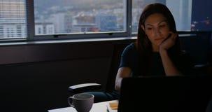 Μπροστινή άποψη της νέας καυκάσιας θηλυκής εκτελεστικής εργασίας στο lap-top στον πίνακα στο σύγχρονο γραφείο 4k φιλμ μικρού μήκους