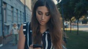 Μπροστινή άποψη της νέας όμορφης γυναίκας που ελέγχει την έξυπνη τηλεφωνικό περιεκτικότητα σε και που περπατά κάτω από το κέντρο  φιλμ μικρού μήκους