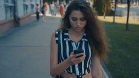 Μπροστινή άποψη της νέας όμορφης γυναίκας που ελέγχει την έξυπνη τηλεφωνικό περιεκτικότητα σε και που περπατά κάτω από το κέντρο  απόθεμα βίντεο
