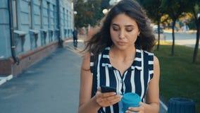 Μπροστινή άποψη της νέας όμορφης γυναίκας που ελέγχει την έξυπνη τηλεφωνικό περιεκτικότητα σε και που πίνει τον καφέ περπατώντας  απόθεμα βίντεο