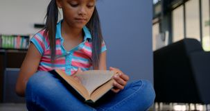 Μπροστινή άποψη της προσεκτικής μαθήτριας αφροαμερικάνων που διαβάζει ένα βιβλίο στη βιβλιοθήκη στο σχολείο 4k απόθεμα βίντεο