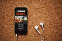Μπροστινή άποψη της σειράς app ροής σε μια κινητή τηλεφωνική οθόνη, κοντά στα άσπρα ακουστικά σε έναν καφετή πίνακα Στοκ εικόνα με δικαίωμα ελεύθερης χρήσης