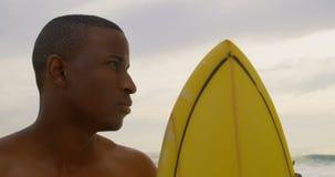 Μπροστινή άποψη του αρσενικού αφροαμερικάνων surfer που στέκεται με την ιστιοσανίδα στην παραλία 4k απόθεμα βίντεο