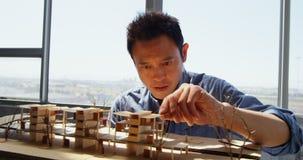 Μπροστινή άποψη του ασιατικού αρσενικού αρχιτέκτονα που εξετάζει το αρχιτεκτονικό πρότυπο σε ένα σύγχρονο γραφείο 4k απόθεμα βίντεο
