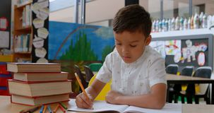 Μπροστινή άποψη του ασιατικού μαθητή που αυξάνει το χέρι μελετώντας στο γραφείο στην τάξη στο σχολείο 4k απόθεμα βίντεο