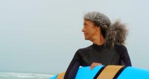Μπροστινή άποψη του δραστήριου ανώτερου θηλυκού αφροαμερικάνων surfer με την ιστιοσανίδα που στέκεται στην παραλία 4k φιλμ μικρού μήκους