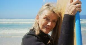 Μπροστινή άποψη του δραστήριου ανώτερου καυκάσιου θηλυκού surfer που στέκεται με την ιστιοσανίδα στην παραλία 4k φιλμ μικρού μήκους