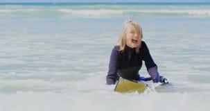 Μπροστινή άποψη του δραστήριου ανώτερου καυκάσιου θηλυκού surfer που κάνει σερφ στη θάλασσα στην ηλιοφάνεια 4k φιλμ μικρού μήκους