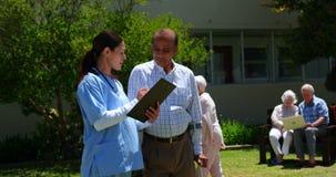 Μπροστινή άποψη του ενεργού ασιατικού ανώτερου ατόμου και του θηλυκού γιατρού που συζητούν πέρα από την ιατρική έκθεση στον κήπο φιλμ μικρού μήκους