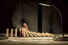 Μπροστινή άποψη του επιχειρηματία που σταματά τα μειωμένα ντόμινο με το χέρι του Στοκ Φωτογραφία