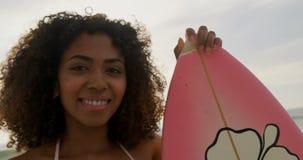 Μπροστινή άποψη του θηλυκού αφροαμερικάνων surfer που στέκεται με την ιστιοσανίδα στην παραλία 4k φιλμ μικρού μήκους