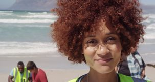 Μπροστινή άποψη του θηλυκού εθελοντή αφροαμερικάνων που εξετάζει τη κάμερα στην παραλία 4k φιλμ μικρού μήκους