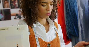 Μπροστινή άποψη του θηλυκού σχεδιαστή μόδας αφροαμερικάνων που εξετάζει τα δείγματα υφασμάτων στο εργαστήριο 4k απόθεμα βίντεο