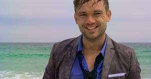 Μπροστινή άποψη του καυκάσιου επιχειρηματία που στέκεται με το χαρτοφύλακα στη θάλασσα στην παραλία 4k απόθεμα βίντεο