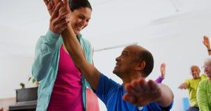 Μπροστινή άποψη του καυκάσιου θηλυκού εκπαιδευτή που εκπαιδεύει το ανώτερο άτομο στην άσκηση στο στούντιο 4k ικανότητας φιλμ μικρού μήκους
