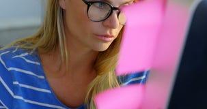 Μπροστινή άποψη του καυκάσιου θηλυκού σχεδιαστή μόδας που εργάζεται στο γραφείο στο γραφείο 4k φιλμ μικρού μήκους