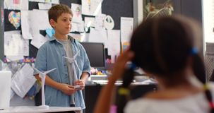 Μπροστινή άποψη του καυκάσιου μαθητή που εξηγεί για το πρότυπο ανεμόμυλων στην τάξη 4k απόθεμα βίντεο