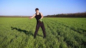 Μπροστινή άποψη του μυϊκού νεαρού άνδρα που συμμετέχεται στην ανύψωση στη ανοιχτή περιοχή Αυξάνει το βάρος με το αριστερό χέρι Ο  απόθεμα βίντεο