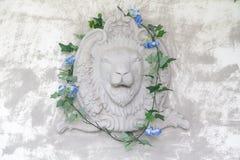Μπροστινή άποψη του νέου επικεφαλής αγάλματος λιονταριών στον τοίχο τσιμέντου με τον κισσό στο ST στοκ φωτογραφία με δικαίωμα ελεύθερης χρήσης
