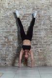 Μπροστινή άποψη του νέου κατάλληλου θηλυκού αθλητή που κάνει handstand την άσκηση ενάντια στο τουβλότοιχο στοκ φωτογραφίες με δικαίωμα ελεύθερης χρήσης