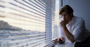 Μπροστινή άποψη του νέου καυκάσιου αρσενικού ανώτερου υπαλλήλου με το χέρι στο πηγούνι που κλίνει στο παράθυρο στο σύγχρονο γραφε φιλμ μικρού μήκους