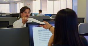 Μπροστινή άποψη του νέου καυκάσιου αρσενικού ανώτερου υπαλλήλου που δίνει τα έγγραφα στο συνάδελφό του στο σύγχρονο γραφείο 4k απόθεμα βίντεο