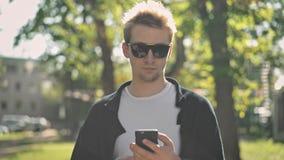 Μπροστινή άποψη του νεαρού άνδρα στα γυαλιά ηλίου που παίρνουν το smartphone από την τσέπη του απόθεμα βίντεο