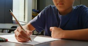 Μπροστινή άποψη του προσεκτικού ασιατικού μαθητή που μελετά στο γραφείο στην τάξη στο σχολείο 4k απόθεμα βίντεο