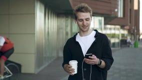 Μπροστινή άποψη του χαμογελώντας νεαρού άνδρα με το smartphone και του καφέ που ακούει τη μουσική απόθεμα βίντεο