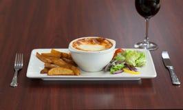 Μπροστινή άποψη του lasagna με τη σαλάτα και τις πατάτες Στοκ Φωτογραφίες