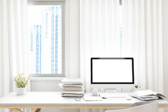 Μπροστινή άποψη του workpark με την κενή άσπρη οθόνη υπολογιστή, το φλυτζάνι καφέ, και το βιβλίο στην εγχώρια εργασία χλεύη επάνω Στοκ Εικόνα