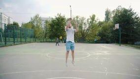 Μπροστινή άποψη των ελεύθερων χτυπημάτων άσκησης παίχτης μπάσκετ υπαίθρια απόθεμα βίντεο